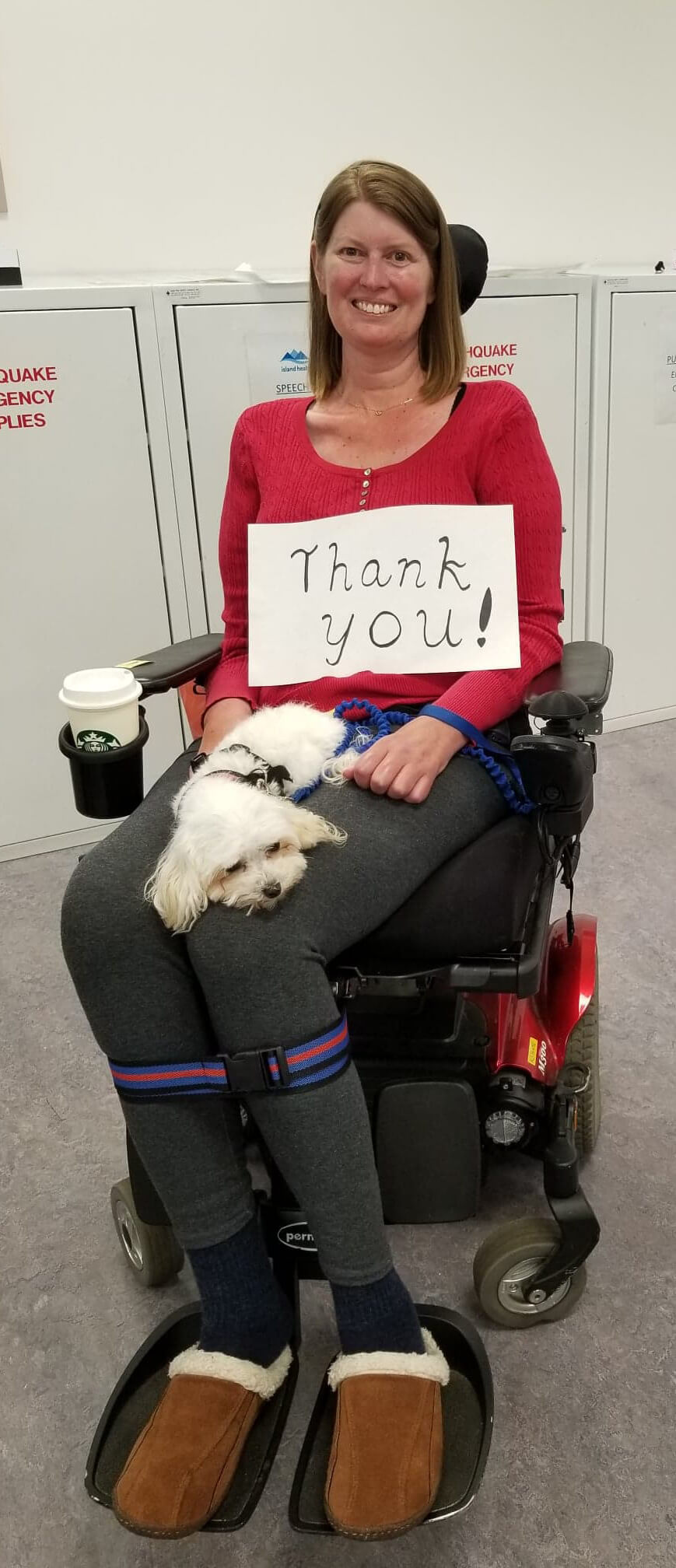 Picture woman in wheelchair smiling with dog on her lap, Thank you sign on her stomach, coffee and slippers