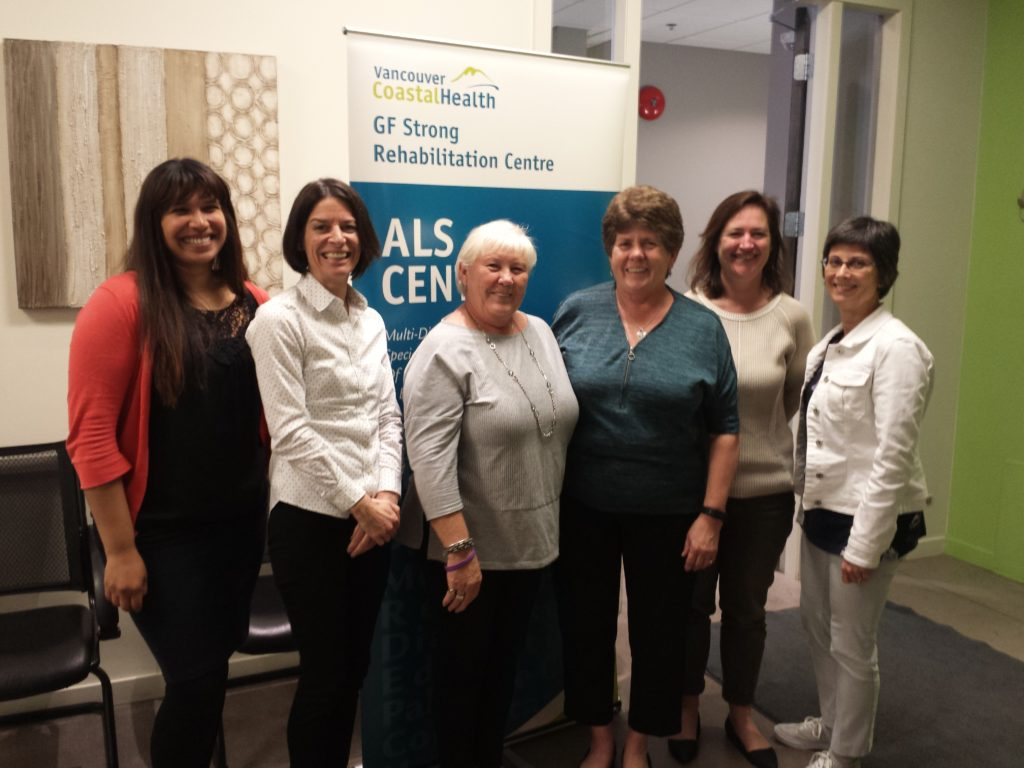 Six women stand smiling in front of a ALS Centre Sign from Vancouver CoastalHealth in the GF Strong Rehabilitation Centre